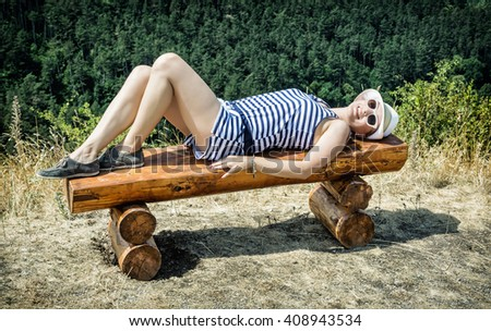 Young caucasian woman with sunhat in sailor outfit is lying on the wooden bench. Beauty and fashion. - stock photo