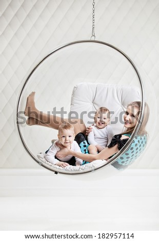 Young Caucasian woman with two babies having fun while sitting in swinging hanging chair  - stock photo