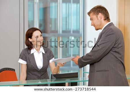 Young caucassian secretary assisting businessman - stock photo