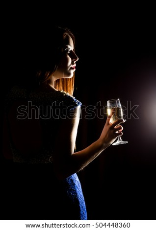 Young celebrating woman in a blue dress holding a glass of champagne on a dark background. play of light and shedow