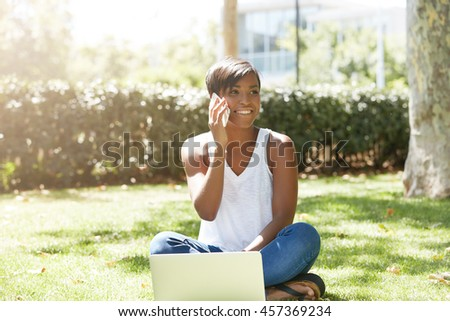 Young charismatic black female business coach sitting on the grass in the park using laptop, talking on mobile phone with asmile, waiting for her trainees to come for training activity outdoors