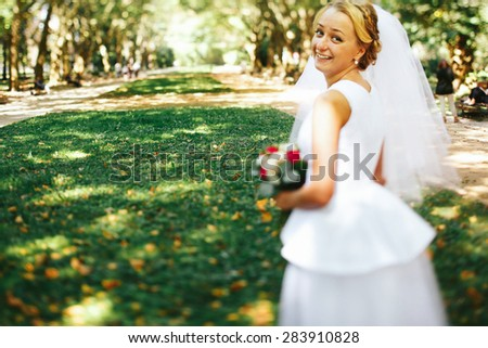 young charming  beautiful stylish blonde bride on the background wonderful spring park - stock photo