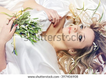 Young charming blonde holding in the hands of snowdrops
