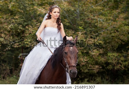 young charming brunette bride in white wedding dress and tracery veil rides on horse