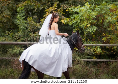 young charming brunette bride in white wedding dress and tracery veil rides on horse - stock photo