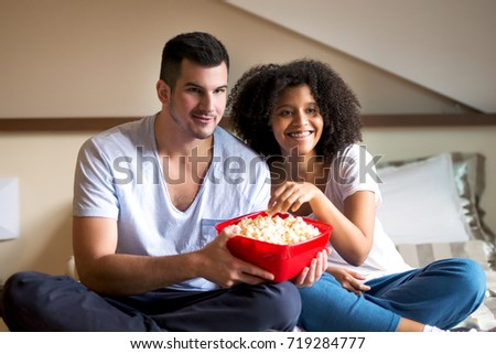 Young charming couple is having a great time with popcorn and movie.