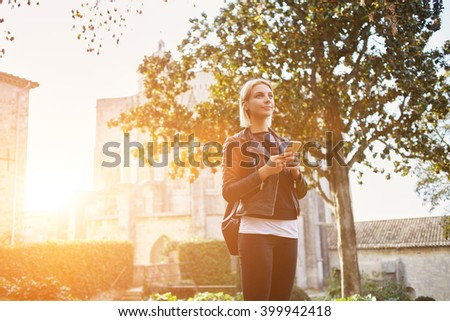 Young charming female dressed in fashionable clothes is holding mobile phone, while is looking away for someone. Stylish hipster girl with cell telephone in hands standing outdoors near university - stock photo