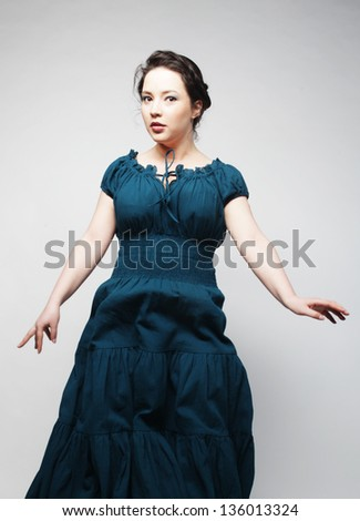 Young charming female in blue dress jumping over grey background - stock photo