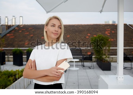 Young charming female is dreaming about something good, while is standing with mobile phone on a terrace cafe. Thoughtful woman skilled CEO is looking away and waiting for a call on cell telephone