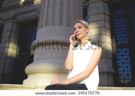 Young charming female student sits near university during break between lectures and calls with smart phone, attractive Caucasian woman relaxes in the fresh air and talks via her cell telephone - stock photo