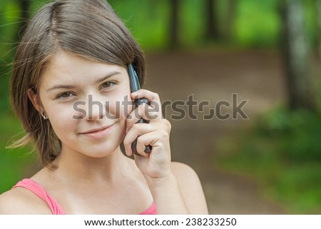 Young charming girl talks by mobile phone and laughs. - stock photo