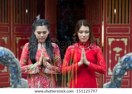 Young charming ladies praying in the Buddhist temple on the foreground