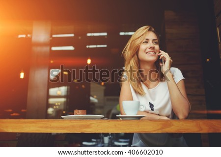 Young charming woman calling with cell telephone while sitting alone in coffee shop during free time, attractive female with cute smile having talking conversation with mobile phone while rest in cafe - stock photo