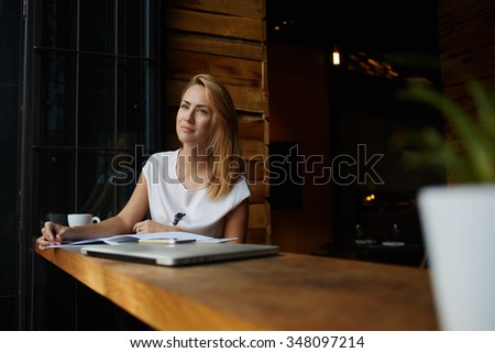 Young charming woman dreaming about something while sitting with magazine in modern coffee shop interior, thoughtful female looking away while relaxing after work on portable computer during lunch  - stock photo