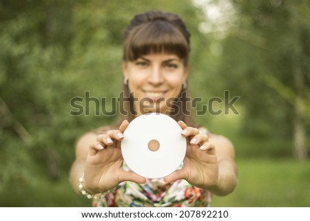 Young charming  woman holds empty and white multimedia disk and smiles, in green summer park. Young European / Caucasian female model. - stock photo
