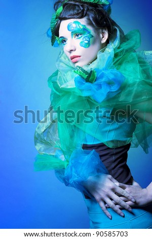 Young charming woman in face-art and with green leaves in her hair