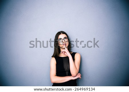 Young charming woman in glasses with finger over lips standing over gray background. Looking up at copyspace. Wearing in black fashion dress - stock photo