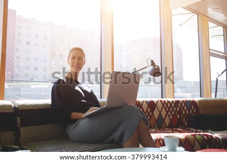 Young charming woman with beautiful smile thinking about something good while waiting until downloads the movie on net-book, cheerful female dreaming while sitting with laptop computer in modern cafe - stock photo