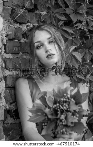 Young charming woman with long blond hair with a professional make-up is the ruins of a brick wall with branches of wild grapes on the ruins of an urbex industrial building with a bouquet of viburnum