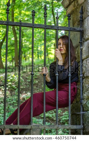 Young charming woman with long hair offender, sits behind bars in an ancient stone castle fortress prison prisoner and looks pityingly through steel bars begging for freedom
