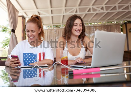 Young charming women working on mobile phone and laptop computer while sitting together in cafe bar, stylish hipster girls using cell telephone and net-book during morning breakfast in coffee shop  - stock photo