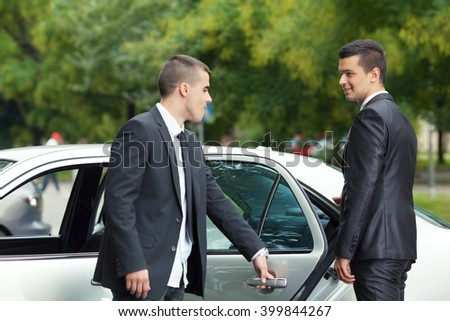 Young chauffeur is holding the door for the young businessman getting into the car