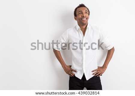 Young cheerful african american businessman on light background with copy space - stock photo