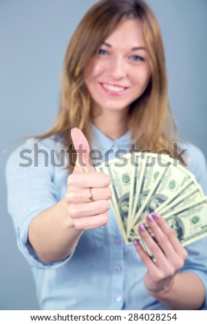 Young cheerful american businesswoman holding money and showing thumbs up in the blue background. Concept - thumb up, woman, dollar, dollar us. Happy young woman showing fun of dollars and thumbs up.