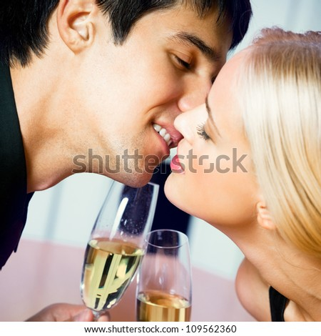 Young cheerful amorous kissing couple with champagne on romantic date or celebrating at restaurant - stock photo