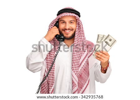 Young cheerful Arab talking on a telephone and holding few stacks of money isolated on white background - stock photo