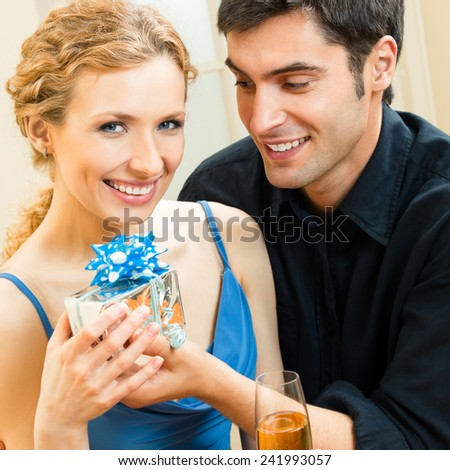Young cheerful attractive couple celebrating with champagne and gift, indoors
