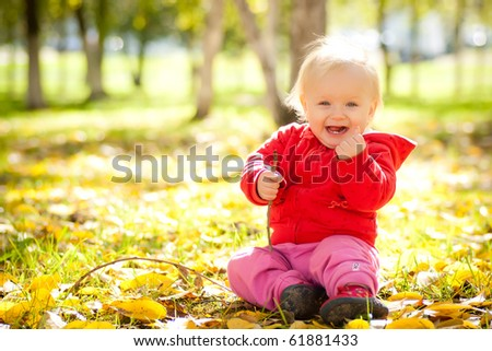 young cheerful baby play with wooden brench under trees in park