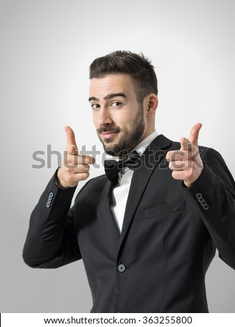 Young cheerful bearded man pointing finger gun gesture at camera. Desaturated portrait over gray studio background with retro vignette.