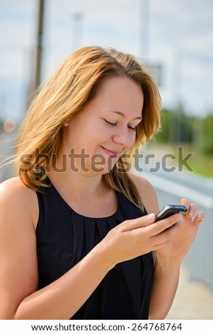 Young cheerful beautiful female in black top using mobile phone. Shallow depth of field. Focus on the left eye - stock photo