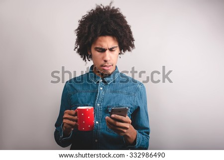 Young cheerful black man typing something on the mobile phone with cup of tea - stock photo