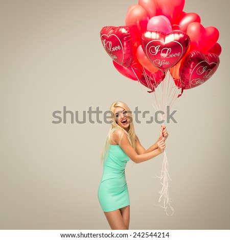 young cheerful blond woman with red balloons - stock photo