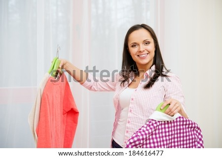 Young cheerful brunette woman choosing clothes in home interior