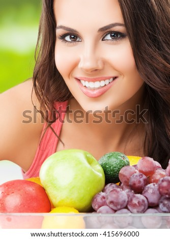 Young cheerful brunette woman with plate of fruits, outdoors. Healthy eating, beauty and dieting concept. - stock photo