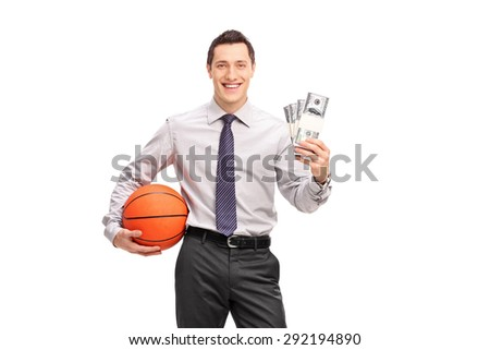 Young cheerful businessman holding a basketball and four stacks of money isolated on white background - stock photo