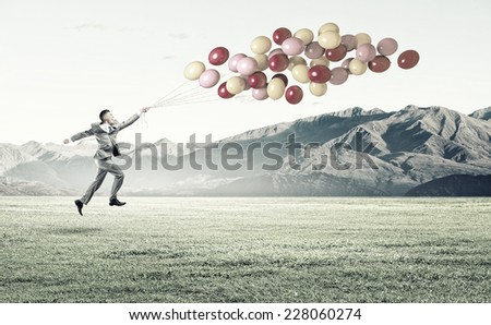 Young cheerful businessman running with bunch of colorful balloons - stock photo