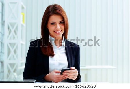 Young cheerful businesswoman holding smartphone on her workplace in office - stock photo