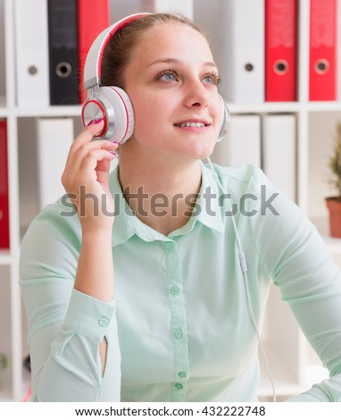 Young cheerful businesswoman listening music in headphones at office - stock photo