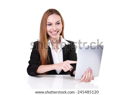 Young cheerful businesswoman using digital tablet pc and sit at the table on her workplace in office, caucasian - stock photo