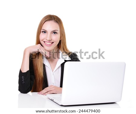 Young cheerful businesswoman using laptop and sit at the table on her workplace in office, caucasian - stock photo