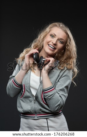 young cheerful casual caucasian woman with headphones over gray background