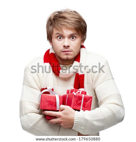 young cheerful caucasian man holding many red christmas gifts with funny expression - stock photo