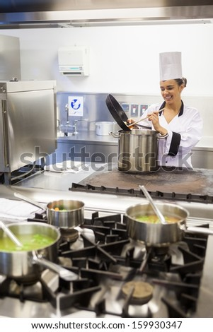 Young cheerful chef preparing meal in professional kitchen