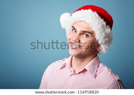 young cheerful christmas man with santa's hat over blue background - stock photo
