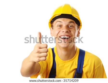 Young cheerful construction worker showing thumb up sign, isolated over white - stock photo