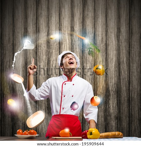 Young cheerful cook and ingredients flying in air - stock photo